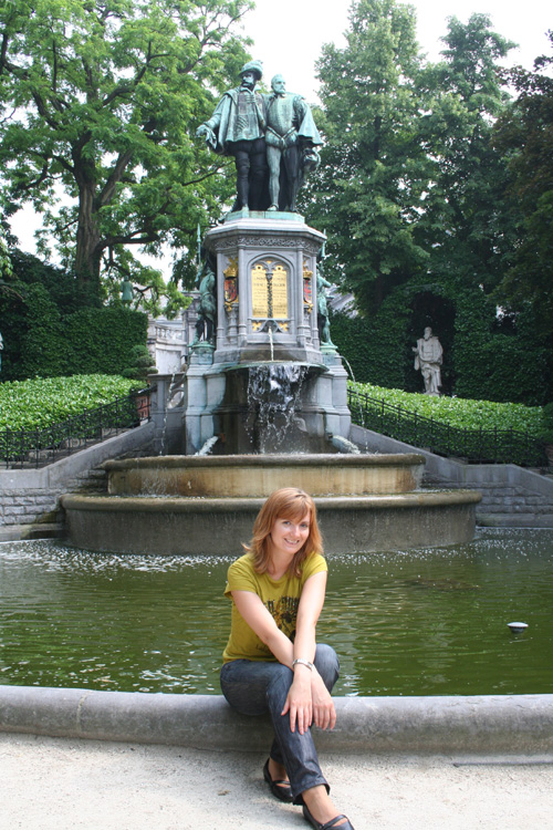 Iwona sitting in front of a fountain at Place du Petit Sablon