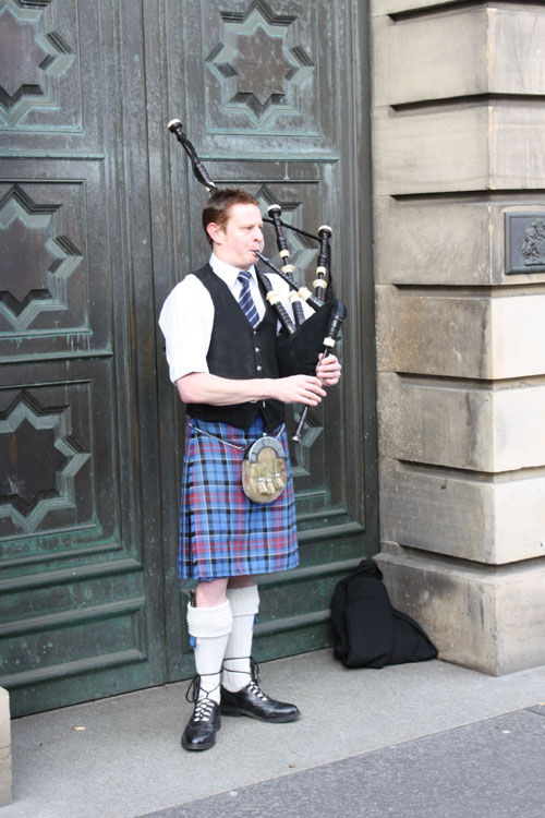 ... man wearing a kilt and playing backpipe
